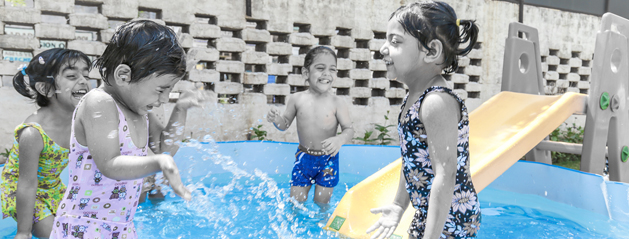 Kids enjoying splash pool in summer camp activities
